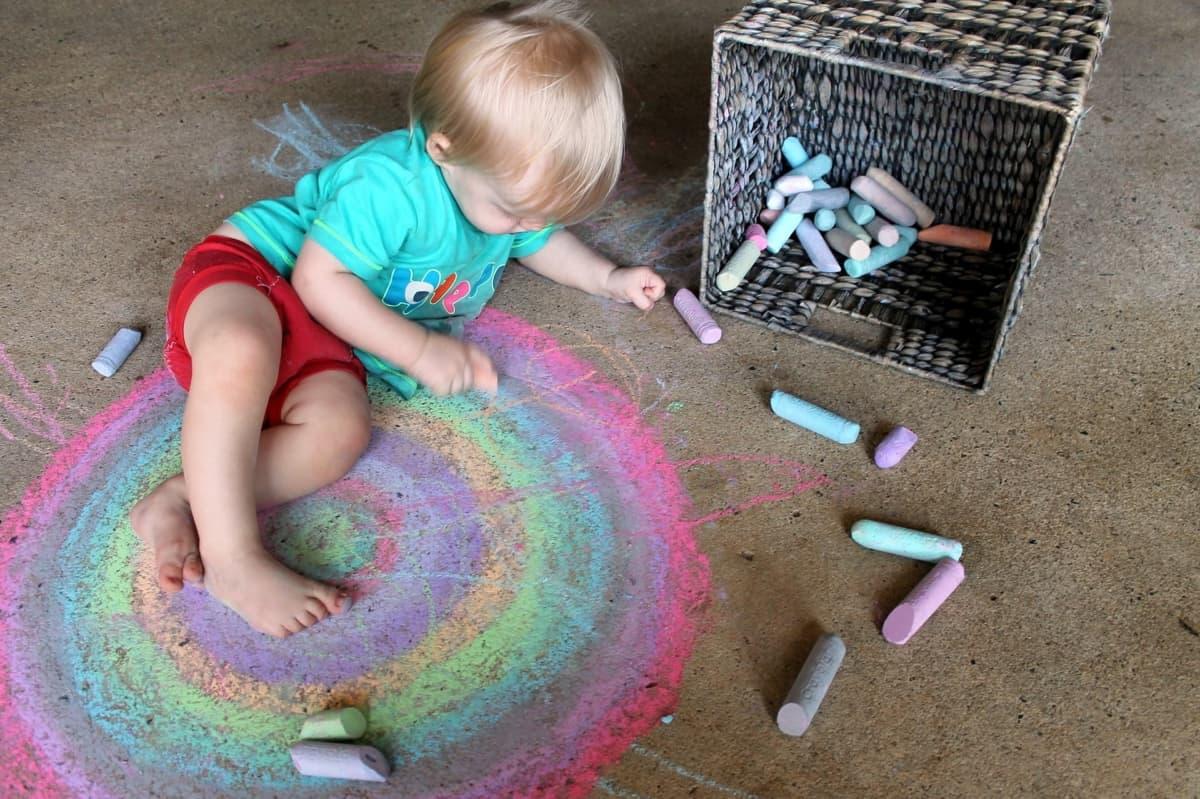Kleines Kind malt mit Tafelkreide auf dem Fußboden